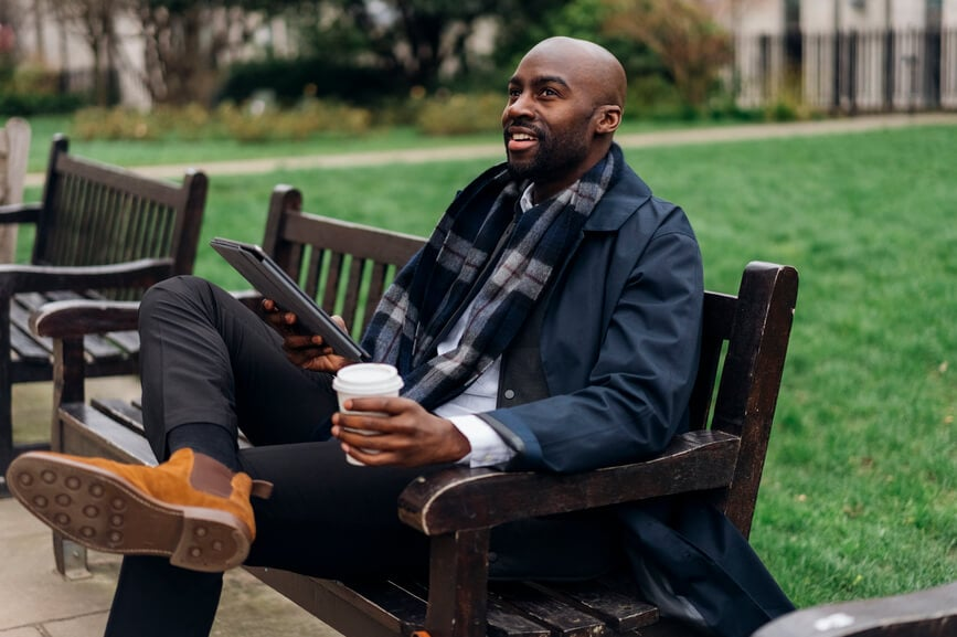 A Black businessman holding a tablet and a coffee relaxes on a park bench.