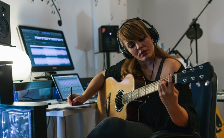 Woman recording guitar in her home sound studio