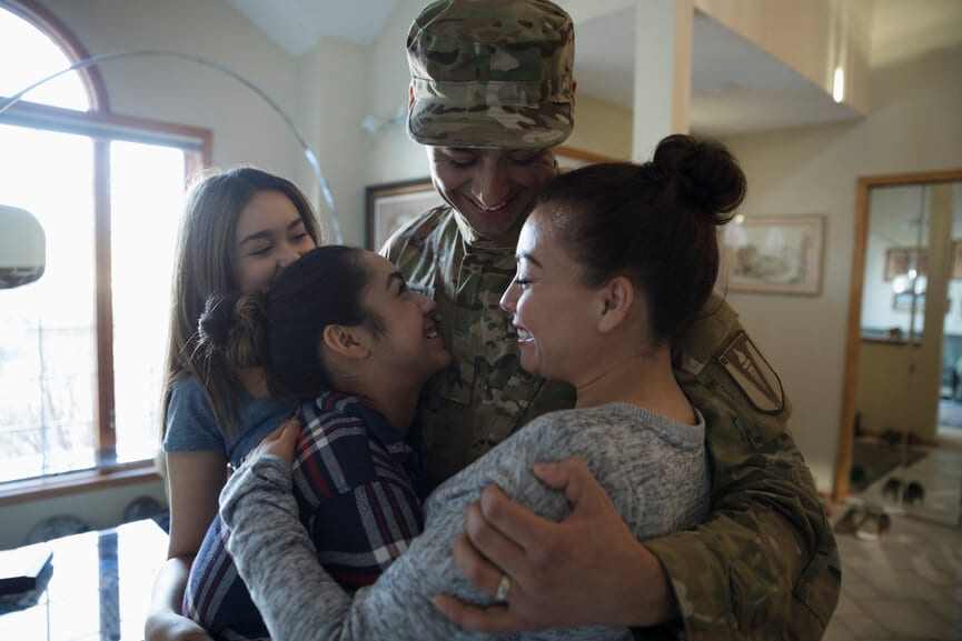 American military member hugging his family.