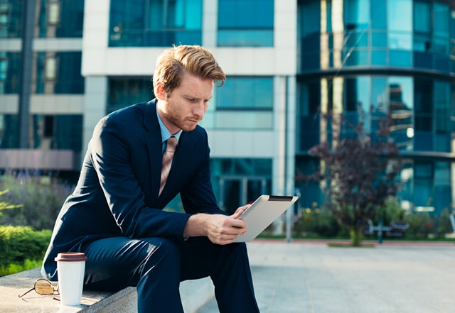 young man in business attire reading on his tablet outside of an office building