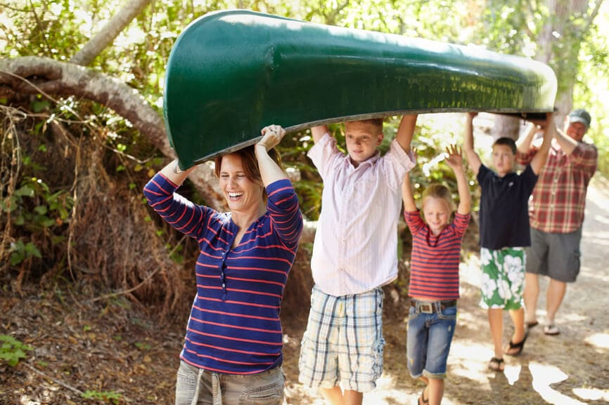 Happy family of five carrying a canoe over their heads on the way to the lake.