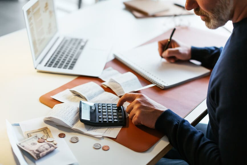Man at his desk using a calculator and working on his taxes.