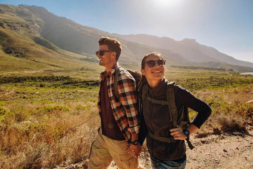 A couple enjoying the sunshine and landscape on a hike.