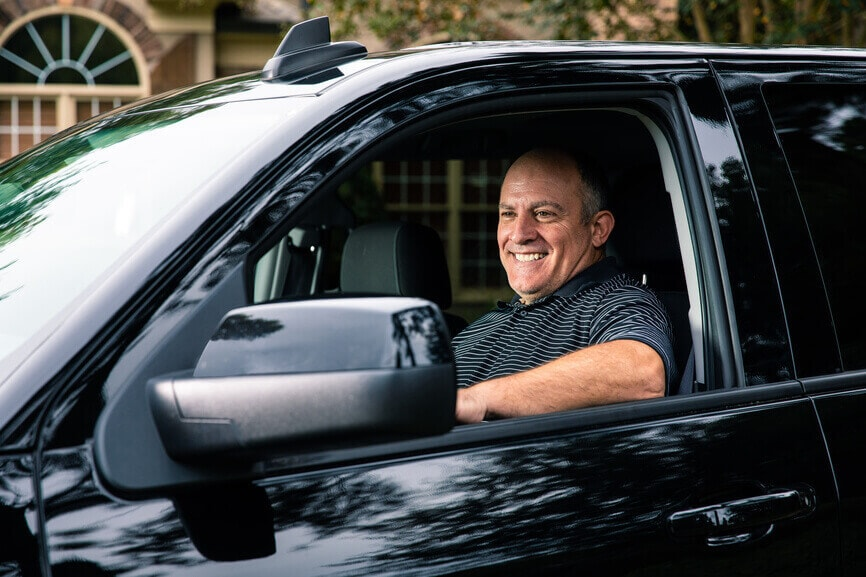 Smiling man driving his new truck.
