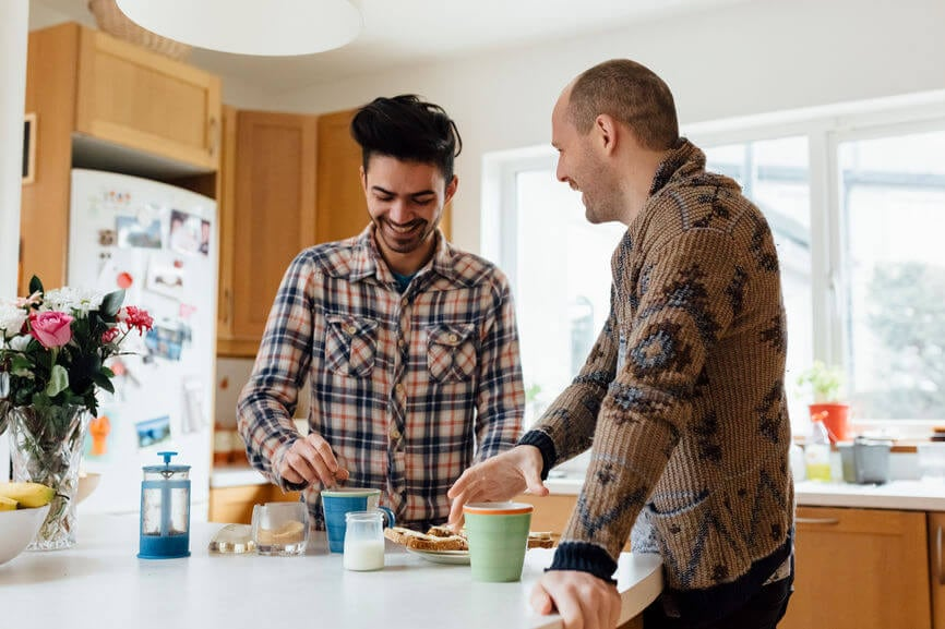 Two men talking and having coffee together in the kitchen.