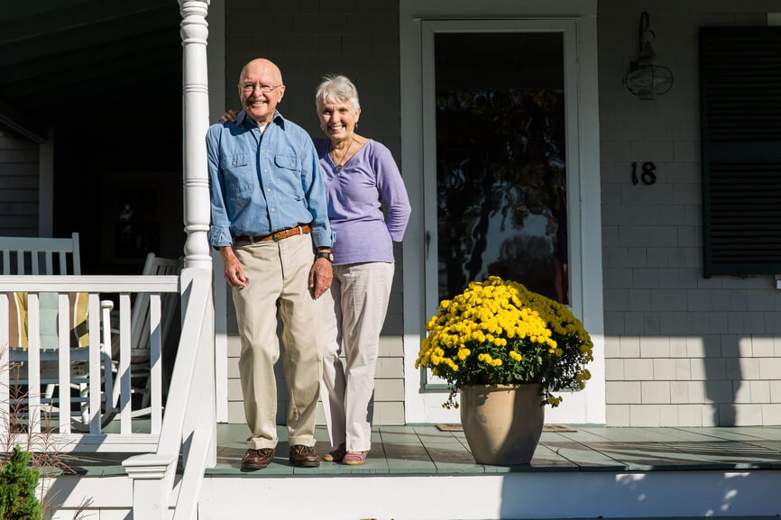 Senior couple enjoying the sunshine on their front porch.