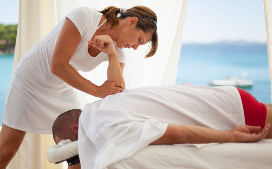 Massage therapist working on a client in a beach setting