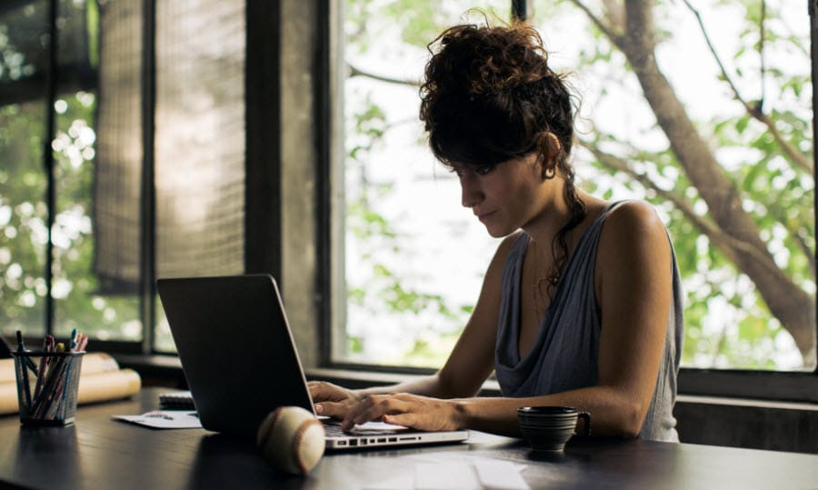 Woman sitting by large windows working on her laptop at a dark brown desk