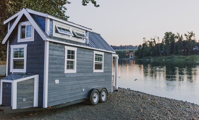 Tiny house on wheels next to a lake