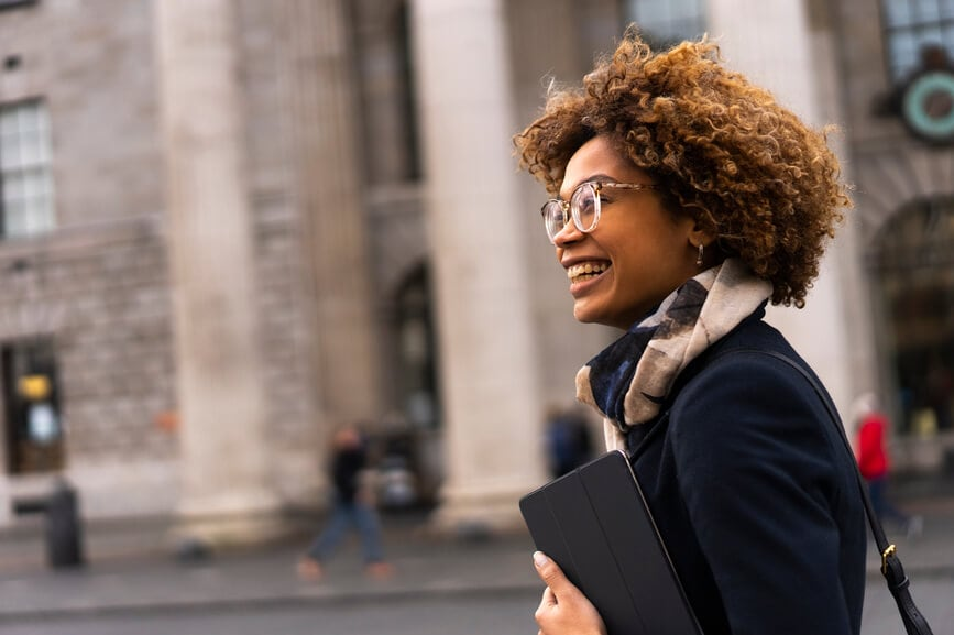A Black woman smiles as she walks down the street holding a laptop case.