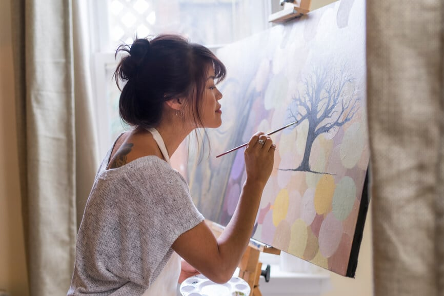 Woman artist painting in her studio