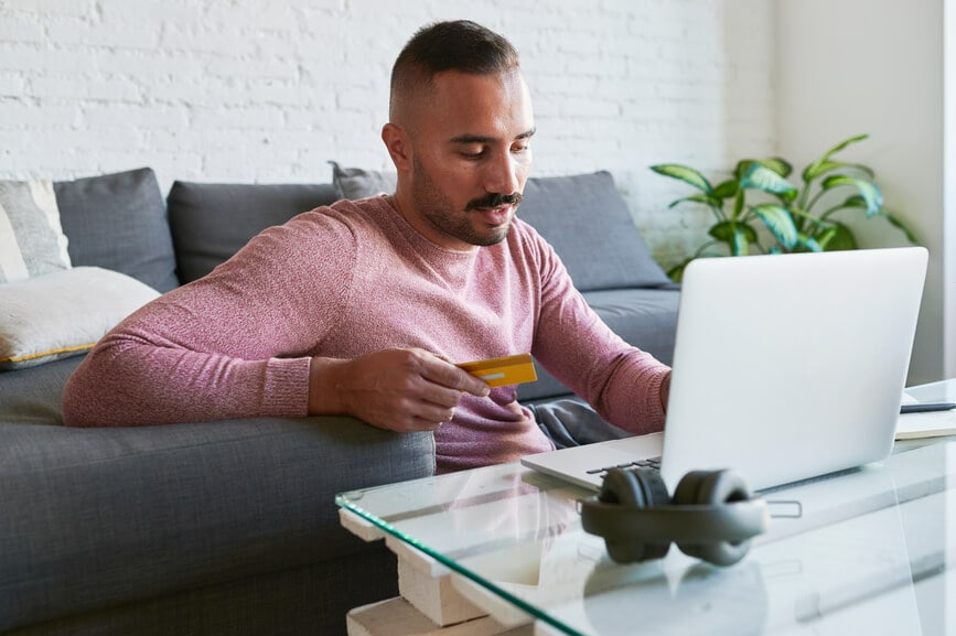 Man pays bills at coffee table with credit card and laptop