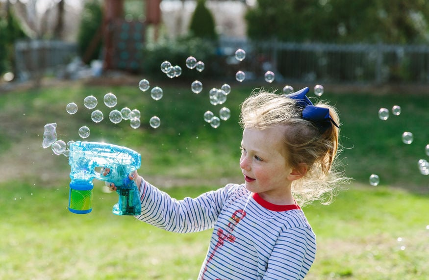 Young girl playing with a bubble maker.
