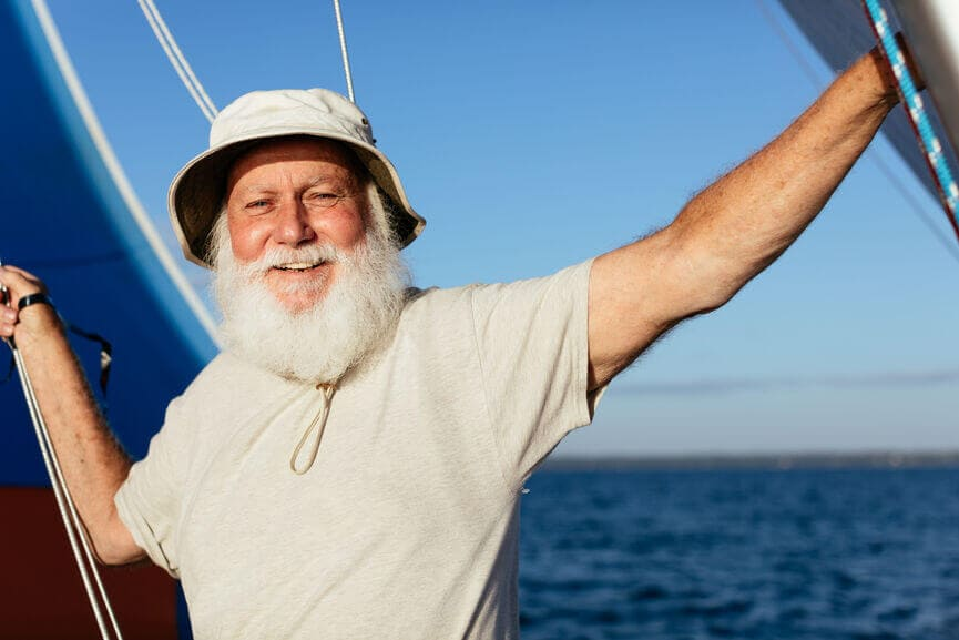 Happy man with a beard on a sailboat