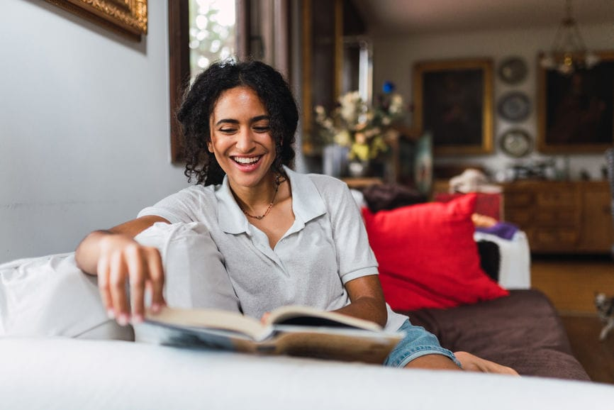 Smiling woman reading a book on the sofa.