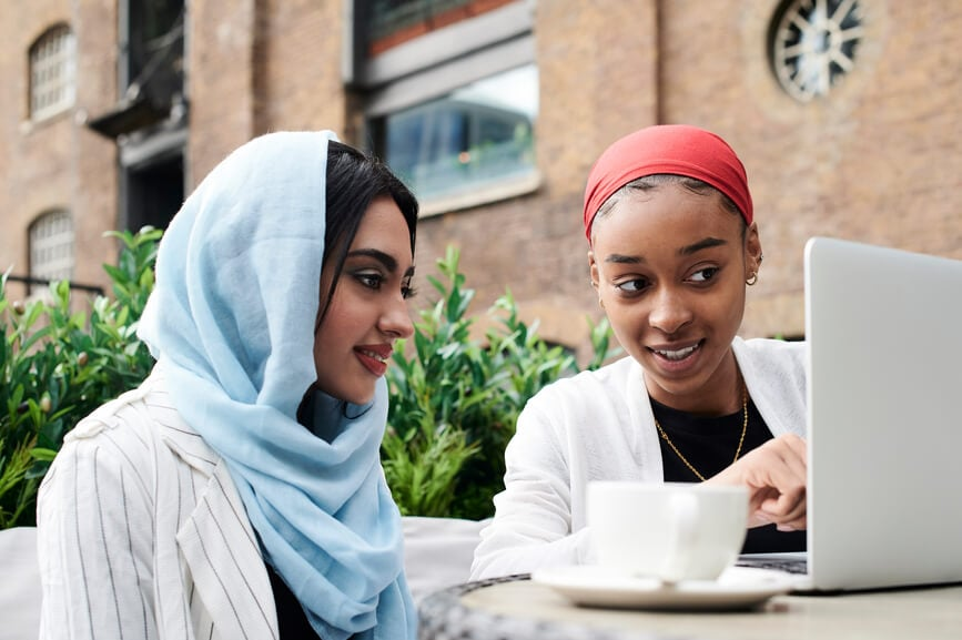 Muslim girl friends using sitting in a cafe having tea and reading from a laptop.