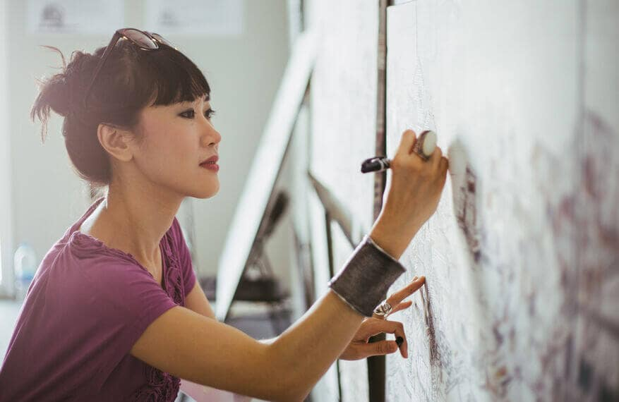 Woman artist drawing on a canvas.
