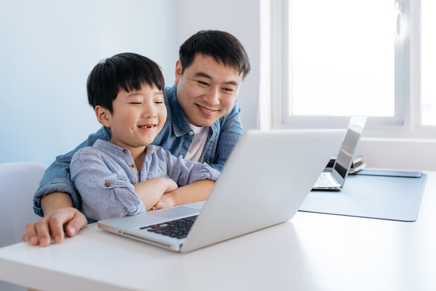 Father at home helping son with online school work.