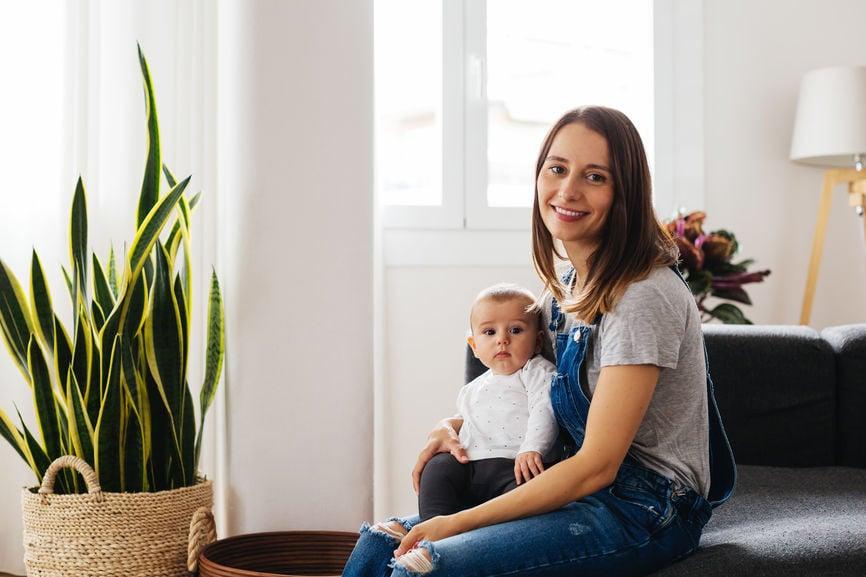 微笑和拿着婴儿的少妇在她的膝部