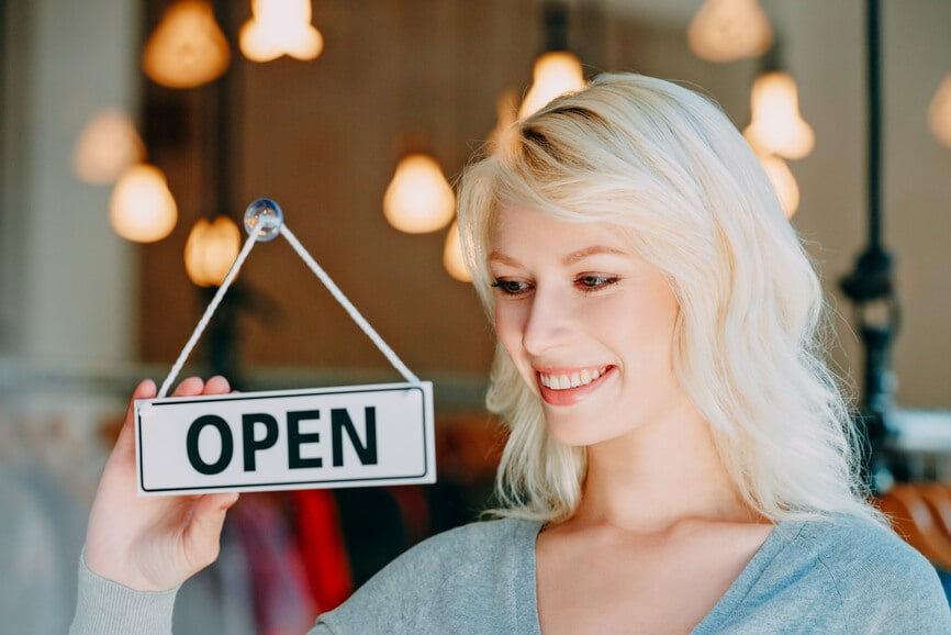Small business owner flipping her shop sign to say Open