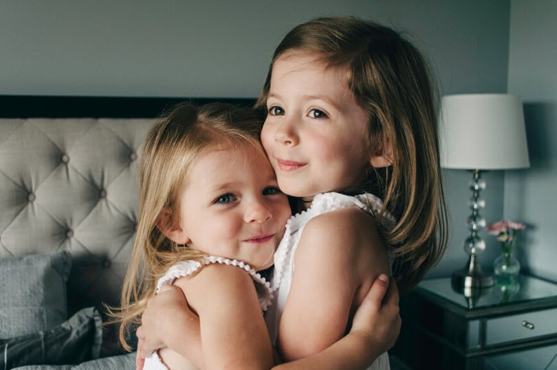 Two girls hugging and smiling