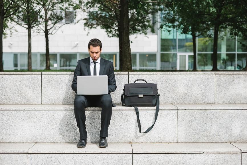 一个在办公大楼外用笔记本电脑工作的商人。