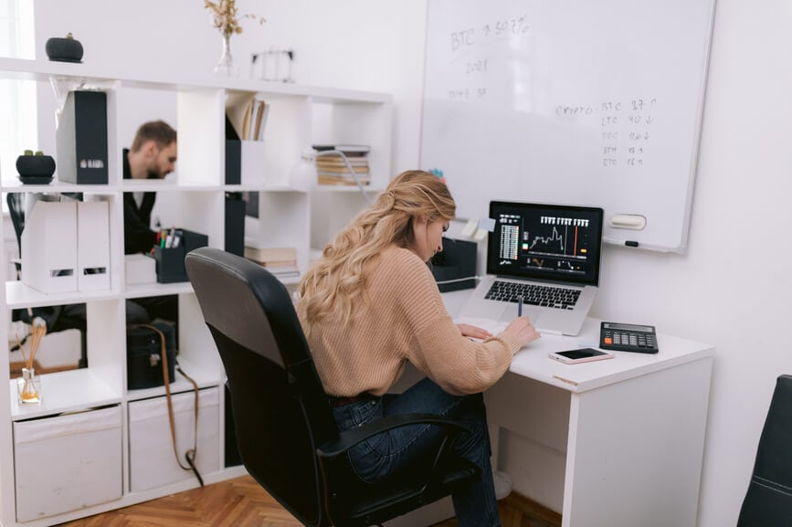 A female trader sits at a desk with a laptop and analyzes stock data.