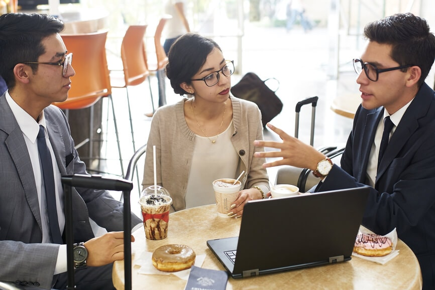 3 young business people discussing investment options at the coffee shop.