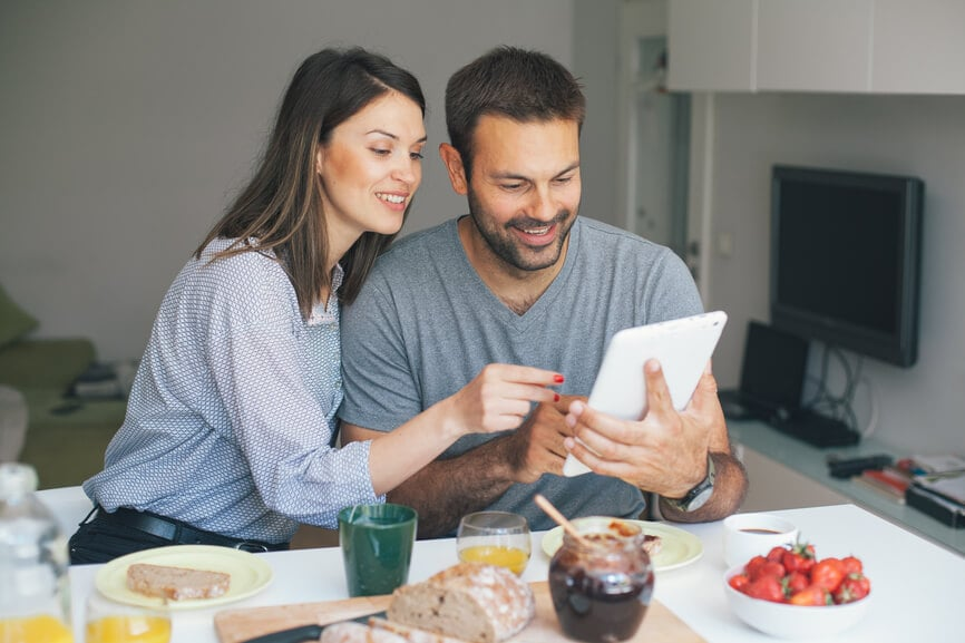 Happy couple having breakfast and looking at their IRA contributions.