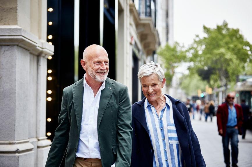 Happy senior couple walking on sidewalk in city