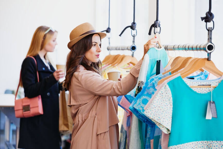 two friends shopping in a boutique clothing store