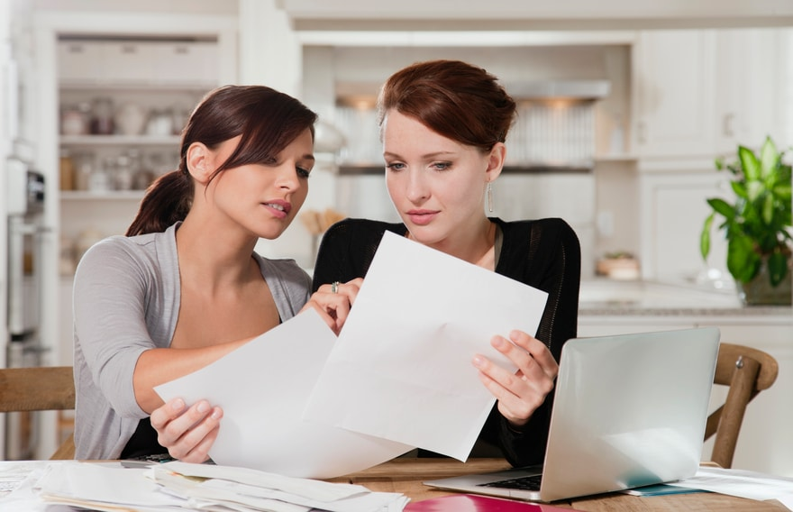 Two women overlooking paperwork