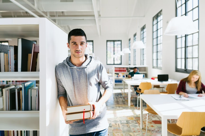 Young University Man Holding Books In A Library.