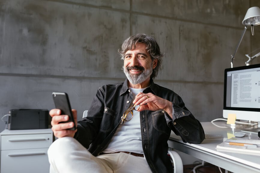 Delighted bearded senior employee with glasses smiling and looking at camera while sitting near desk and using smartphone during break in office.