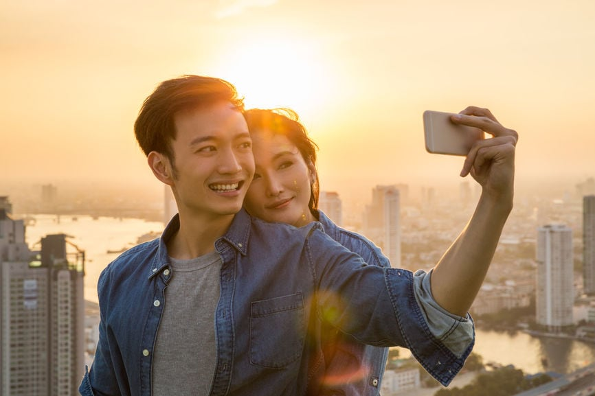 Smiling Young Couple Taking A Selfie At Sunset