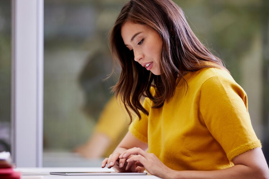 Serious businesswoman using digital tablet at desk in office