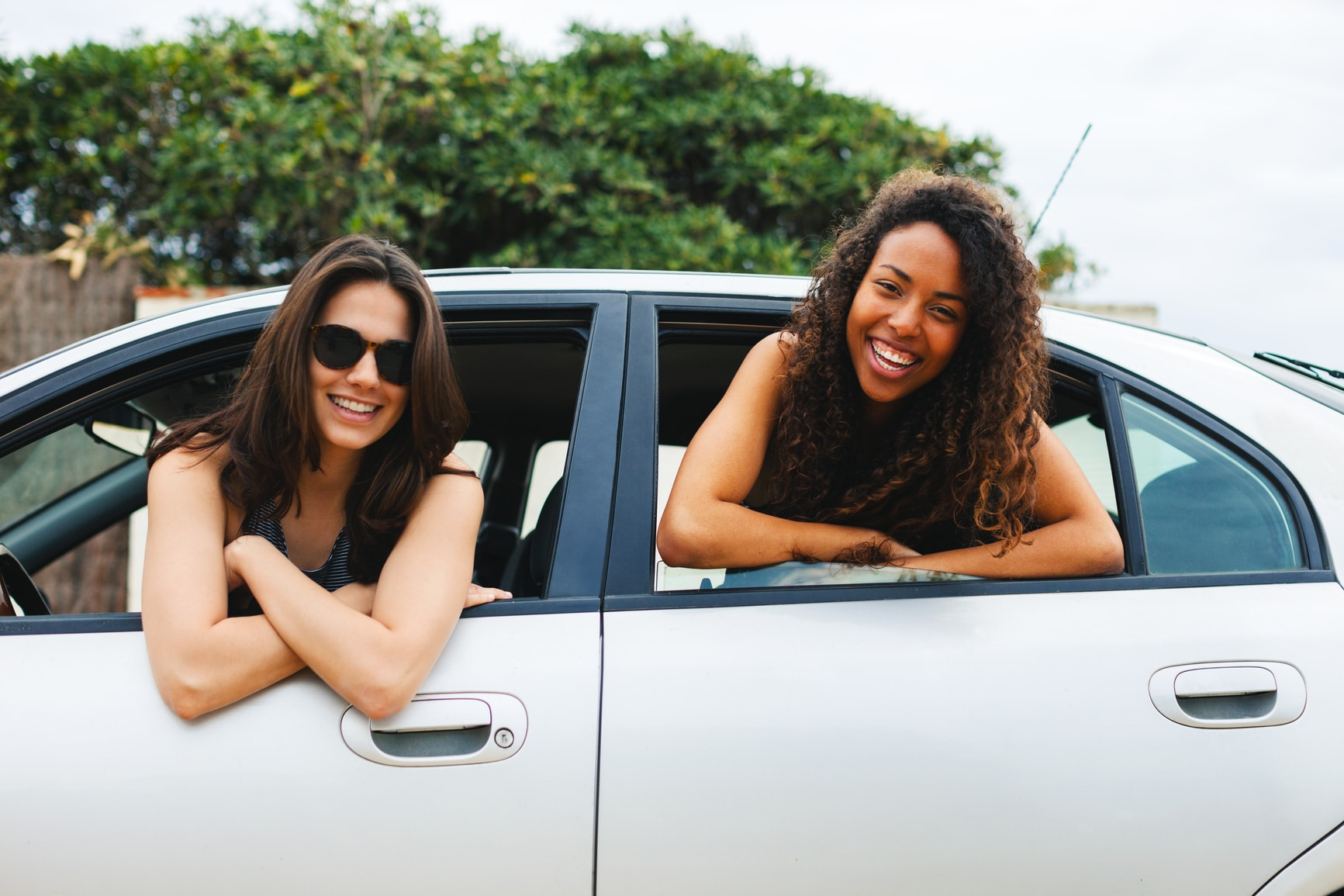 Two girls smiling outside of car window