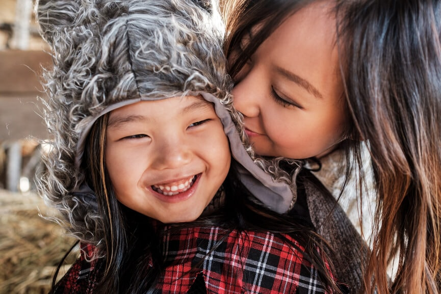 Mother kissing her smiling young daughter during fall season.