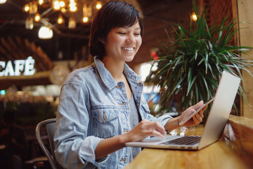 Young smiling woman working on her laptop in a coffee shop.