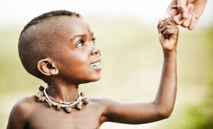 Smiling African child holding a person's hand