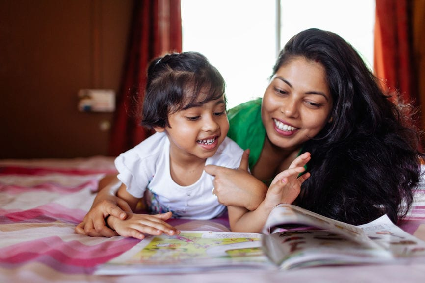 Little Girl Sharing A Cheerful Moment With Her Mother While Studying