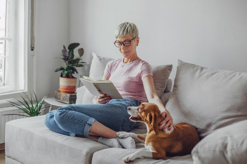 Woman reading on the couch with her dog.