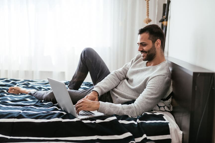 Self-employed man at home using his laptop to look for freelance work.