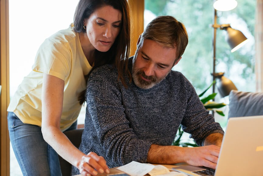 Adult focused woman and bearded man at home looking at 401k loan options.
