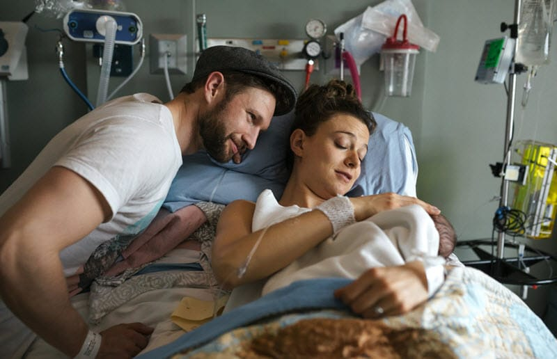 Couple holding newborn in hospital bed