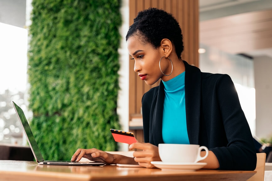 A Black woman holding a credit card makes a payment on her laptop.