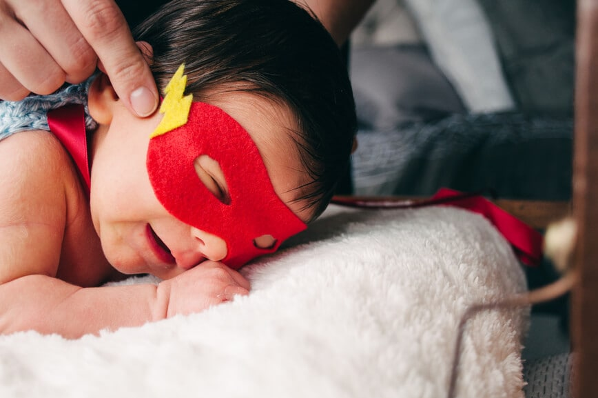 newborn infant sleeping with a hero mask on