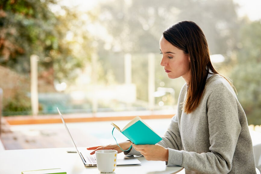Young business woman writing in her planner and working on laptop at home