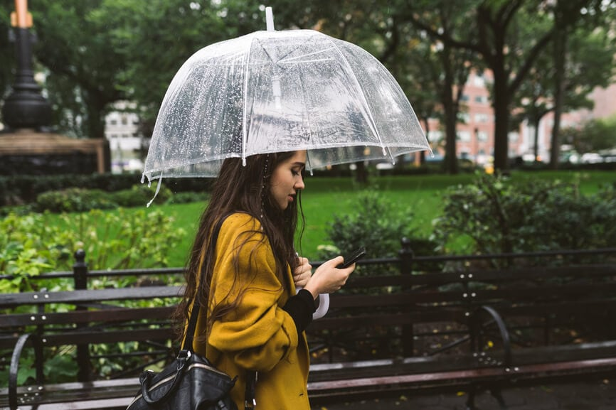 Woman standing in the rain with an umbrella and reading on her smart phone.