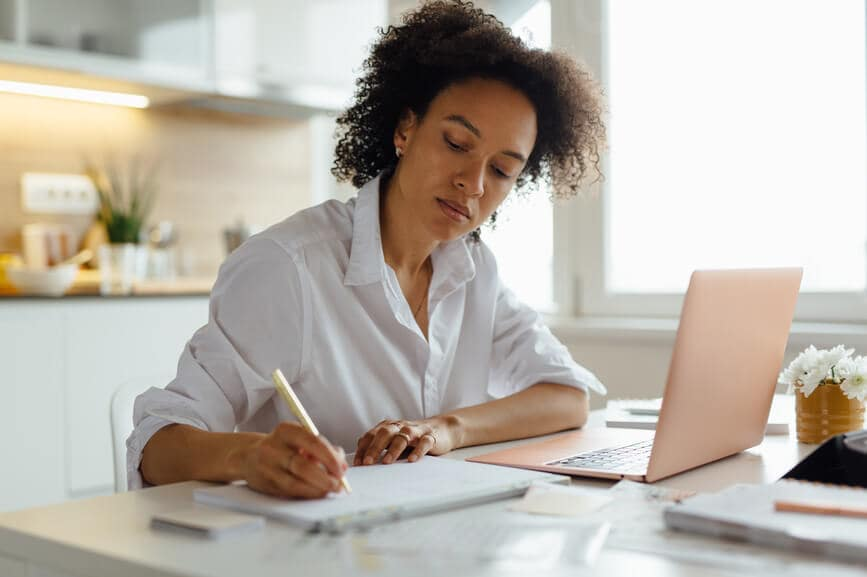 A woman works at a table with a laptop and notepad